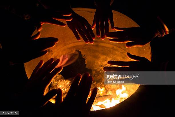 Refugee men keep warm by a fire at the 'No Border Kitchen' on March 27 2016 in Mytilene Greece The 'No Border Kitchen is a small camp on a beach near...