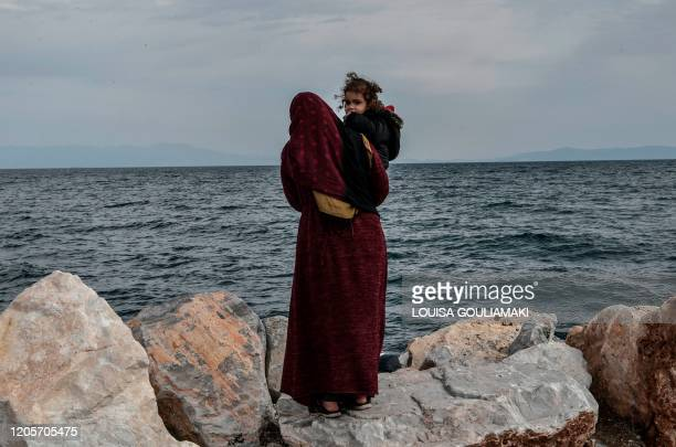 A refugee mother holds her child as she stands looking out at sea at he port of Mytilene on the Greek Island of Lesbos on March 7 close to where a...