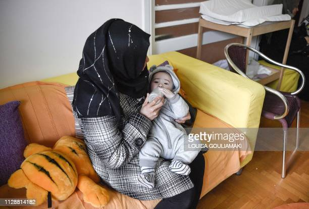 A refugee mother holds her son in a centre for refugee women and their babies run by the Amurtel NGO in Athens' Victoria Square on January 30 2019 In...