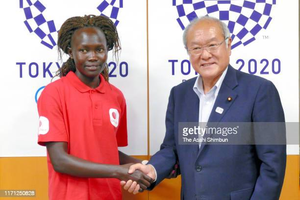 Refugee Olympic Team Athlete Rose Lokonyen of South Sudan and Olympic Minister Shunichi Suzuki shake hands during their meeting on August 29, 2019 in...