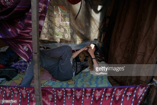 A refugee play his phone as he settling on the roadside in front of the overcapacity immigration detention house in Jakarta Indonesia on June 19 2018...