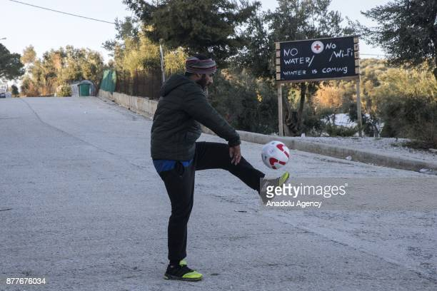 A refugee plays with a soccer ball at the Moria Refugee Camp in Lesbos Greece on November 21 2017 Overpopulated refugee camp is comprised mostly of...