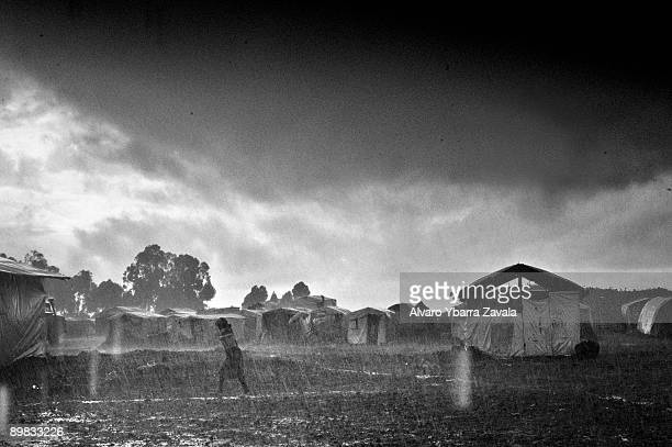 A refugee runs for shelter in the rain in the Kibati refugee camp