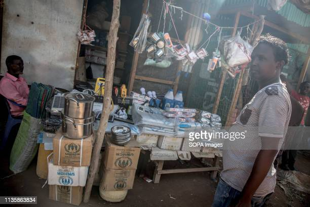 Refugee seen standing in front of a shop stand where UNHCR-distributed pots and pans are being sold in the refugee camp. Dadaab is one of the largest...