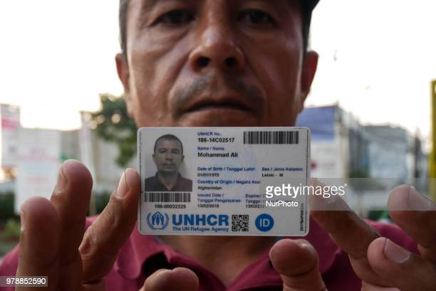 A refugee shows his UNHCR card as they settling on the roadside in front of the overcapacity immigration detention house in Jakarta Indonesia on June...