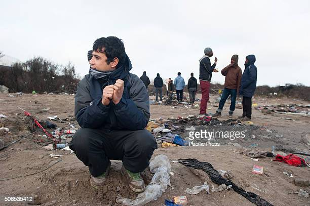 A refugee sits in between the trash of a part of the refugee camp that got evicted at the jungle of Calais