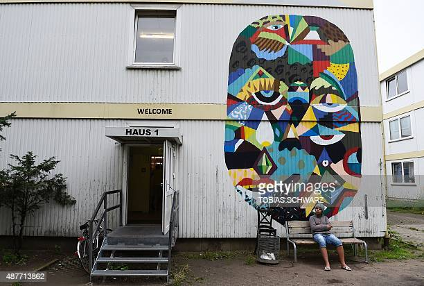 A refugee sits outside house one of a temporary refugee home in Berlin's Spandau district on September 11 2015 The unprecedented influx of refugees...