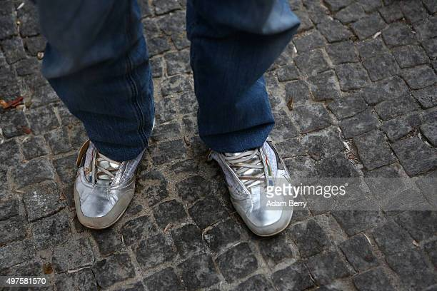 A refugee stands in donated shoes as he waits outside the LaGeSo State Office for Health and Social Services the office for registering migrants on...