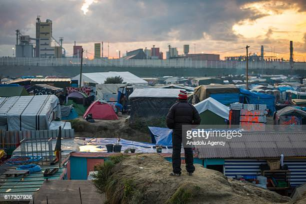 A refugee stands on a hill at the Calais 'jungle' camp in Calais France on October 22 2016