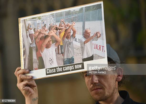 A refugee supporter holds a placard as he and others gather in Sydney on October 5 2016 to mark the milestone of 200 days of continuous protests in...