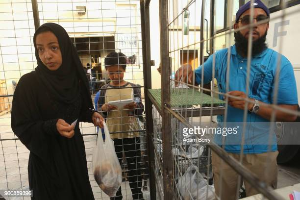 A refugee takes a bag of hot beans and rice at an independent NGOrun food distribution center outside the Moria refugee camp on May 20 2018 in...