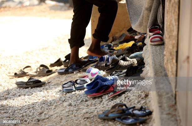 A refugee takes off his shoes at a makeshift mosque at the Moria refugee camp on May 20 2018 in Mytilene Greece Despite being built to hold only 2500...
