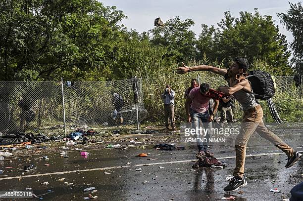 A refugee throws a stone towards Hungarian riot police after they used water cannon and pepper spray to push back refugees at the Hungarian border...