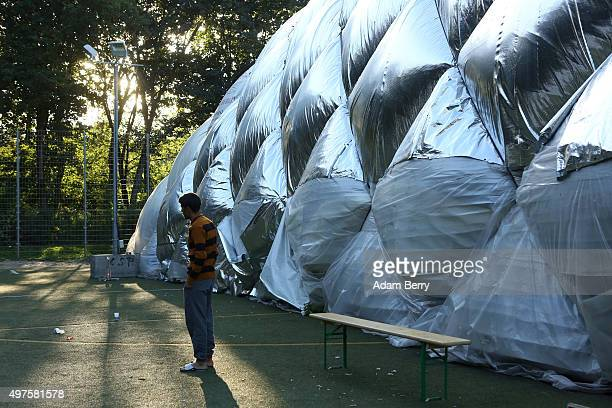 A refugee walks outside of an airdome used as a temporary shelter for refugees on September 26 2015 in Berlin Germany Following the attacks in Paris...