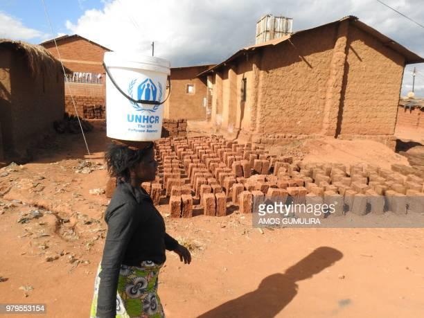 A refugee walks past drying bricks in the Dzaleka Refugee camp on World Refugee Day at Dzaleka Refugee Camp in Dowa District Central region of Malawi...