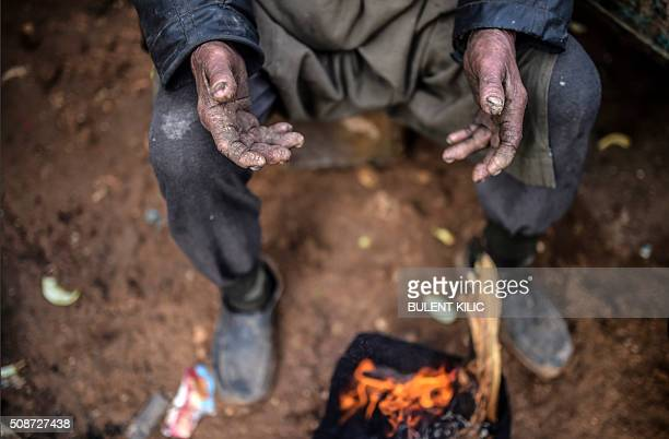 TOPSHOT A refugee warms himself at a bonfire at the Turkish border crossing gate as Syrians fleeing the northern embattled city of Aleppo wait on...