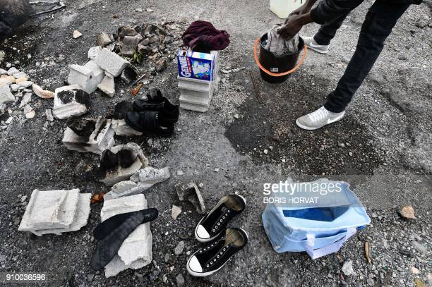 A refugee washes clothes in the Cite des Kalliste a deserted housing complex in the North neighbourhood of Marseille southern France on January 24...