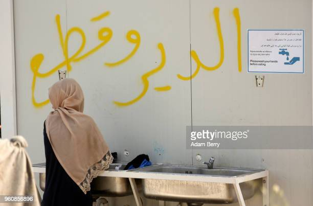 A refugee washes clothing in a sink at the Moria refugee camp on May 20 2018 in Mytilene Greece Despite being built to hold only 2500 people the camp...