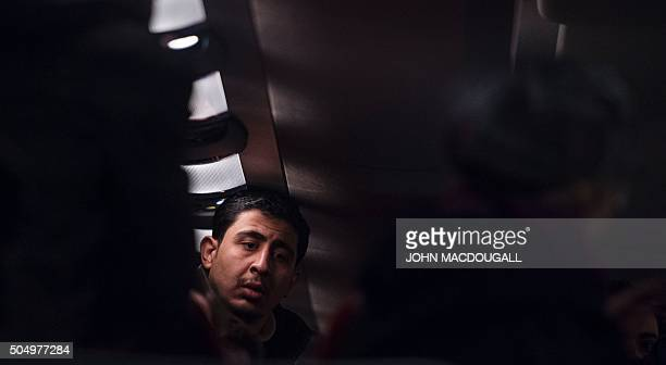 A refugee who has been granted an asylum status sits in a bus in front of the chancellery in Berlin on January 14 after it arrived from the Bavarian...