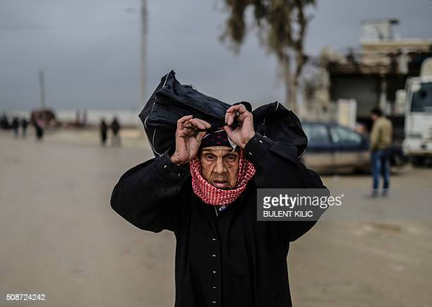 TOPSHOT A refugee woman carries her belongings near the Turkish border crossing gate as Syrians fleeing the northern embattled city of Aleppo wait on...