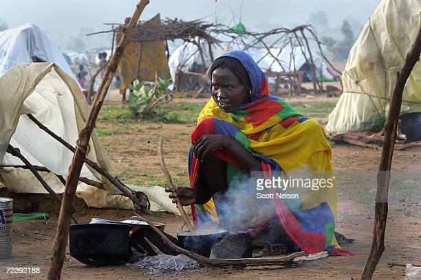 A refugee woman from the Darfur region of Sudan prepares breakfast by her tent in the spontaneous overflow camp outside the Bredjing camp August 29...