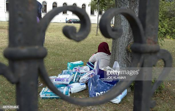 A refugee woman guards packages with nappies for children at Austria's main refugee processing centre in Traiskirchen on July 31 2015 The centre 20...
