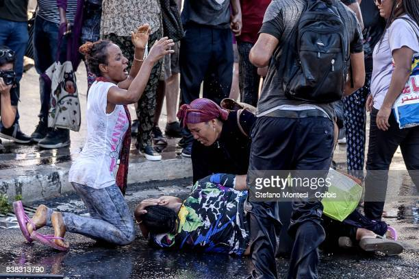 A refugee woman is struck by the water cannons by the police is being rescued by other refugees during the removal of refugees who camped in the...