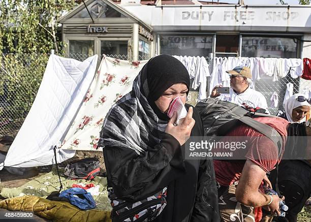 A refugee woman reacts after Hungarian riot police used pepper spray and water cannon to push back refugees at the Hungarian border with Serbia near...