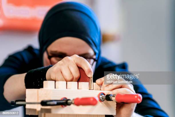 A refugee woman wearing a headscarf works at excercise workshop of Berlin chamber of crafts on October 01 2017 in Berlin Germany