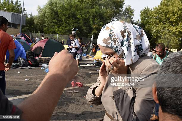 A refugee woman wipes her eyes after Hungarian riot police used pepper spray and water cannon to push back refugees at the Hungarian border with...