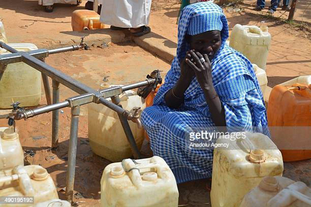 Refugee women wait to get water from a waterwell as they try to live under hard conditions at UNICEF supported refugee camps in Darfur Sudan on...