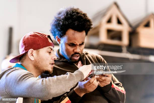A Refugee works next to his trainer at arrivo excercise workshop of Berlin chamber of crafts on October 01 2017 in Berlin Germany