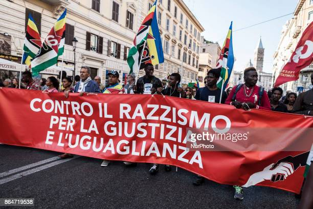 Refugees and asylum seekers hold a banner reading 'Against racism for justice and equality' as they march downtown during the 'Non reato' national...