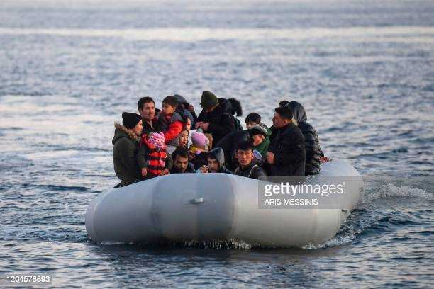 Refugees and migrants aboard an inflatable boat arrive in the Greek island of Lesbos on March 2 2020 Around 500 migrants landed on Sunday morning in...