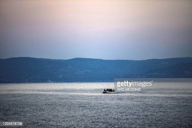 TOPSHOT Refugees and migrants aboard an inflatable boat sail on the sea before arriving on the Greek island of Lesbos on March 2 2020 Around 500...