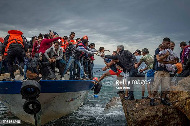 Refugees and Migrants aboard fishing boat drived by smugglers reach the Greek Island coast of Lesbos after crossing the Aegean sea from Turkey on...