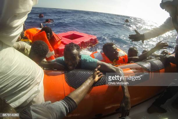 Refugees and migrants are pulled onboard a rescue craft by crewmembers from the Migrant Offshore Aid Station 'Phoenix' vessel after a wooden boat...