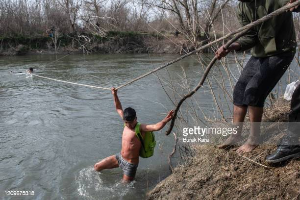 Refugees and migrants are rescued from an island in the middle of Evros river after becoming stucked for the past two days after trying to cross from...