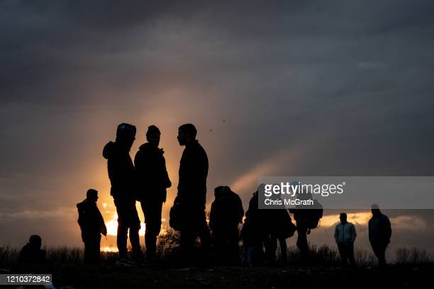 Refugees and migrants are seen at a makeshift camp next to the Edirne Old Bridge on March 04 2020 in Edirne Turkey Thousands of refugees and migrants...