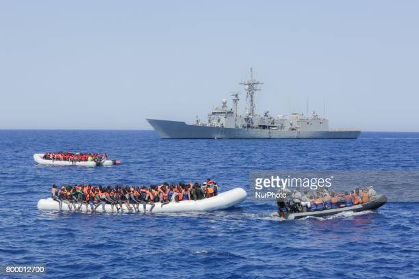 Refugees and migrants are seen floating in an overcrowded rubber boat in front of a European war ship as they wait to be assisted by Italian Cost...