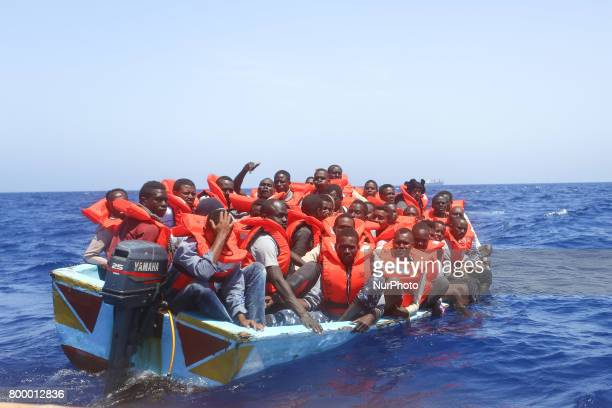 Refugees and migrants are seen floating in an overcrowded wooden boat as they wait to be assisted by search and rescue crew members from NGO SeaEye...