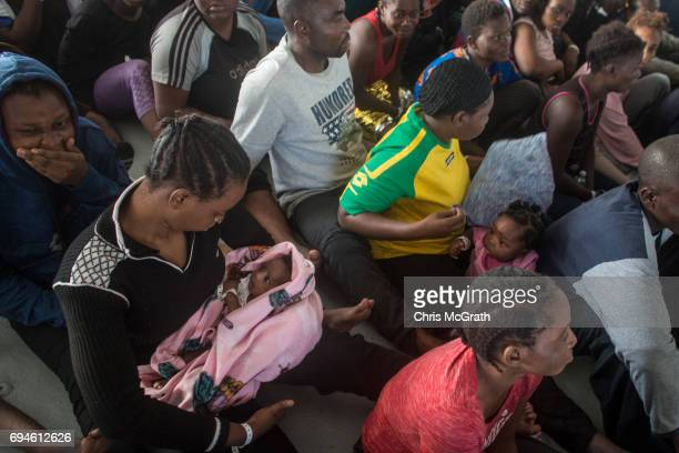 Refugees and migrants are seen onboard the Migrant Offshore Aid Station Phoenix vessel after being rescued at sea earlier in the day on June 10 2017...