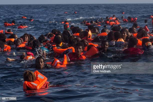 Refugees and migrants are seen swimming and yelling for assistance from crew members from the Migrant Offshore Aid Station 'Phoenix' vessel after a...