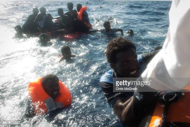 Refugees and migrants are seen swimming towards a rescue craft as a rescue crewmember from the Migrant Offshore Aid Station 'Phoenix' vessel pulls a...