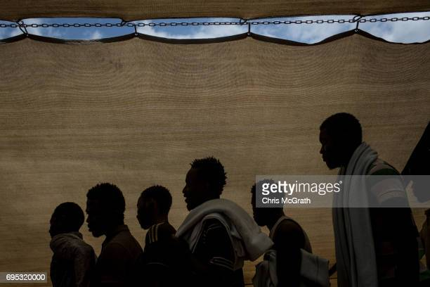Refugees and migrants are seen waiting to disembark the Migrant Offshore Aid Station Phoenix vessel after arriving in port on June 12 2017 in Reggio...