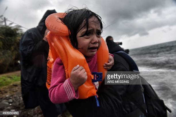 Refugees and migrants arrive at Lesbos island after crossing the Aegean sea from Turkey on October 23 2015 Many Syrian families with small children...