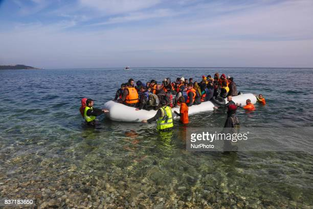 Refugees and migrants arriving at Lesvos island Greece on March 122016 Refugees arriving at Lesvos in a rubber dinghy boat after they flee from their...