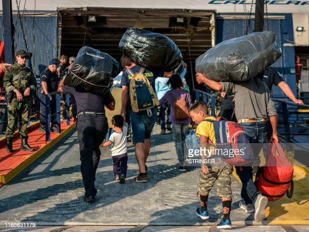 TOPSHOT Refugees and migrants board a ship at the port of Mytilene on the island of Lesbos on September 2 as hundreds of migrants leave Lesbos...