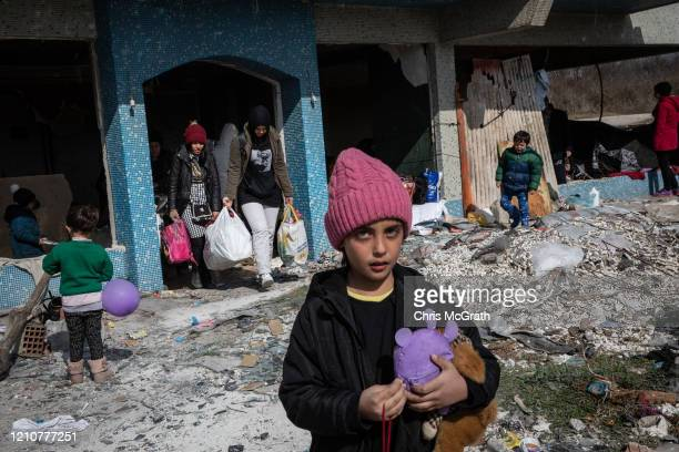 Refugees and migrants carry their belongings from an abandoned building they were staying in next to the bus station after police removed them due to...