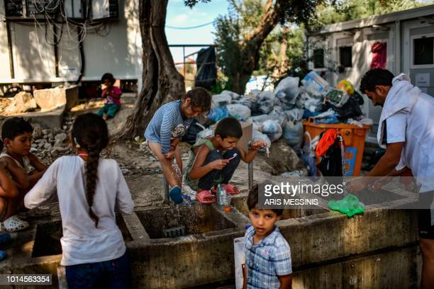 Refugees and migrants clean themselves and wash their clothes at a camp outside the Moria refugee camp in the island of Lesbos on August 5, 2018.